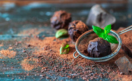 Delicious chocolate truffles with mint, cocoa powder and dark chocolate on a dark wooden background. Imagens