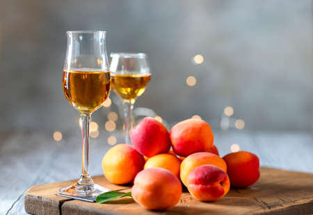 Apricot liqueur in shot glass and fresh apricots on a light wooden table in holiday colorful bokeh. Selective focus
