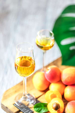 Apricot liqueur in shot glass and fresh apricots on a light wooden table.
