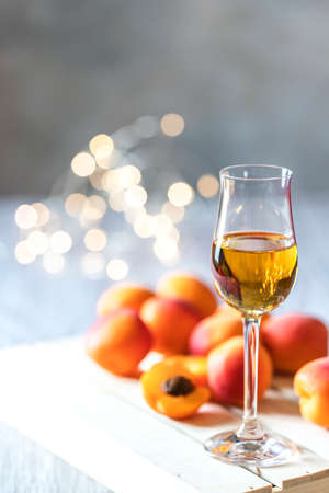Apricot liqueur in shot glass and fresh apricots on a light wooden table in holiday colorful bokeh.