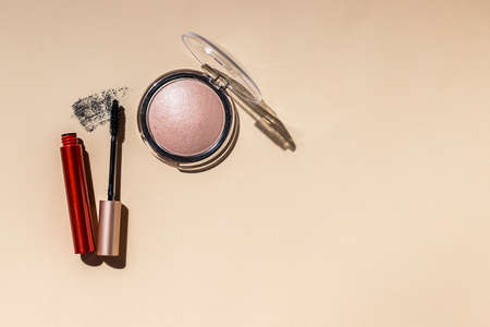 Decorative flat lay composition with cosmetic powder, brush, mascara on beige background. Hard light. Cosmetics and fashion concept.