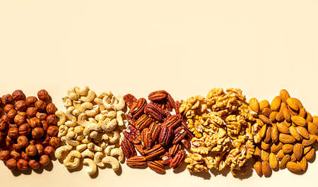 Various nuts on a beige background. Walnuts, almonds, hazelnuts and cashews, pecans. Organic vegetarian food, healthy snacks.