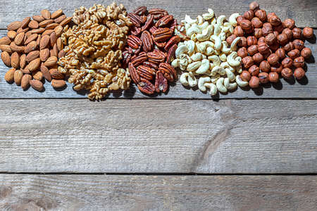 Various nuts on a wooden background. Walnut, almonds, hazelnuts and cashews, pecans. Organic vegetarian food, healthy snacks.
