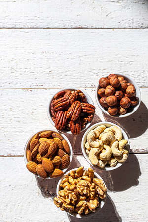 Various nuts in bowls on a white wooden background. Walnut, almonds, hazelnuts and cashews, pecans. Organic vegetarian food, healthy snacks. Imagens