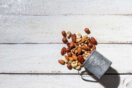 Various nuts on a white wooden background. Walnut, almonds, hazelnuts and cashews, pecans. Organic vegetarian food, healthy snacks.