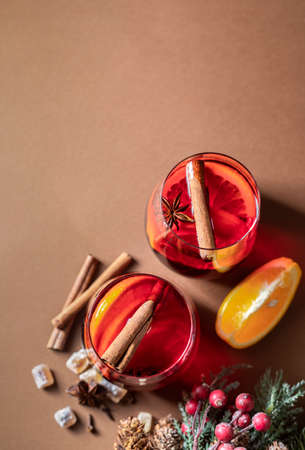 Hot Christmas mulled wine in glass mug with orange slices, cinnamon, anise in a glass cup. Imagens