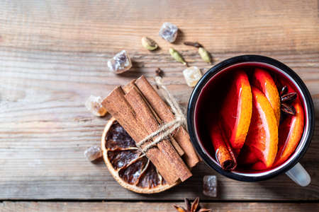Hot christmas mulled red wine with spices and fruits on a wooden rustic table. Imagens