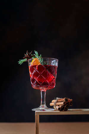 Hot Christmas mulled wine with orange slices, cinnamon, anise in a glass cup on a dark background. Imagens