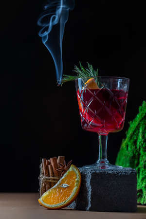 Hot Christmas mulled wine cup on a creative stone podium on a dark background garnished with smoking rosemary sprigs.