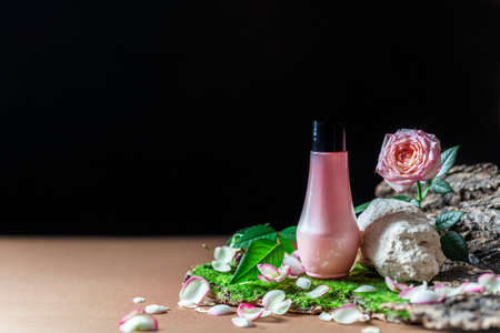 Pink tube of cosmetic product on a creative stone podium on a dark background. Trendy natural spa concept.