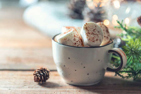 Hot cocoa with marshmallow surrounded by winter things on a wooden table. Winter holiday.