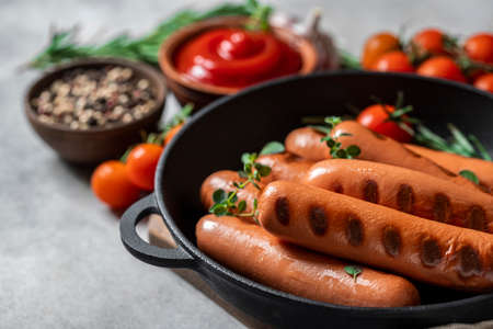 Roasted sausages in cast-iron frying pan over concrete background.