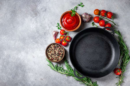 Cast iron pan and spices on a concrete background with copy space. Empty iron pan.