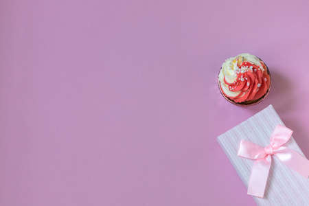Composition with festive cupcake with pink cream and gift box on pink background. Natural light.