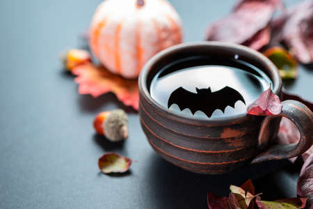 The shadow of the Halloween bat reflected in a cup of tea on a dark background. Halloween celebration concept.