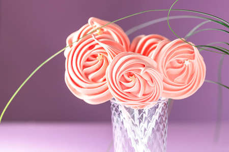 Close-up of meringues in a glass on pink background. Sweets for children.