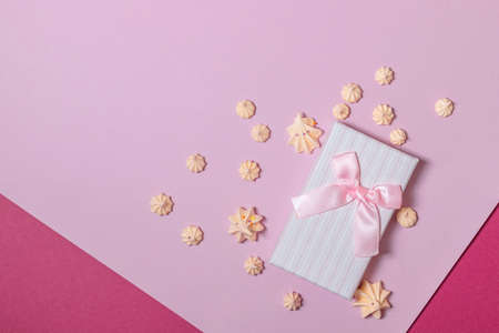 Top view of pink gift box and marshmallow on pink background.