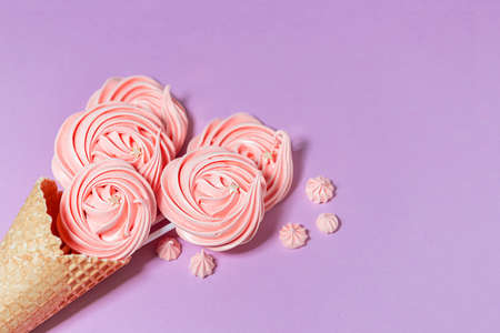 Top view of crispy ice cream waffle cone and marshmallows on pink background.