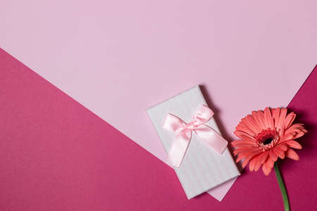 Top view of pink gift box and flower on pink background.