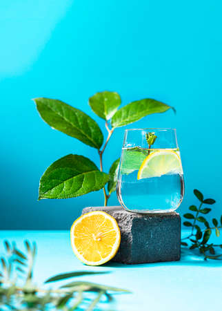 A glass of water with lemon and mint on pedestal in fashion trendy style on a blue background.