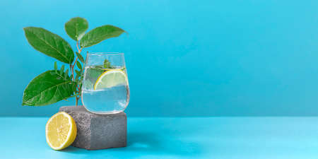 A glass of water with lemon and mint on pedestal in fashion trendy style on a blue background. Banner
