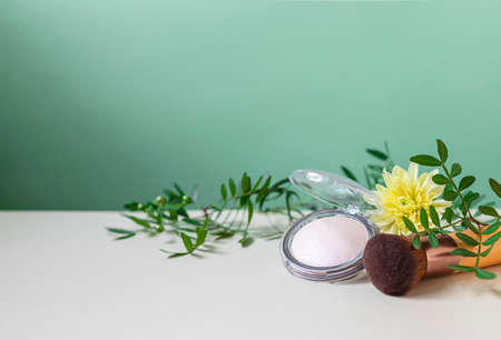 Mineral powder foundation with brush on pedestal in fashion trendy style on a green background.