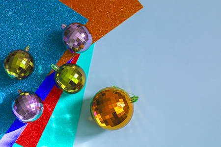 Disco mirror ball Christmas tree toy on a bright festive layered paper. Christmas and New Year holiday concept.