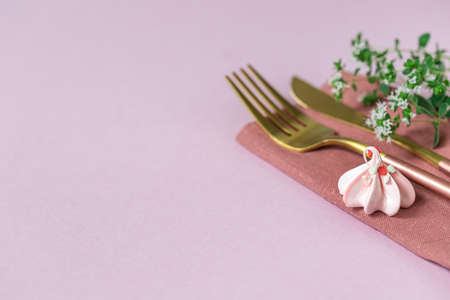 Pink meringue, knife and fork and linen napkin on a pink background. Celebration. Copy space