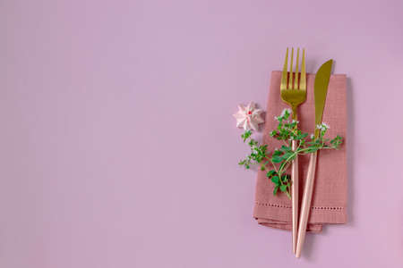 Knife and fork and linen napkin on pink background. Holiday celebration. Copy space