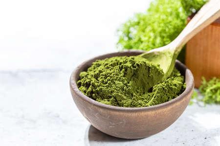 Green powder chlorella, spirulina on gray concrete background. Concept dieting, detox, healthy superfood, which contains protein. Stock Photo