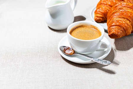 Croissants and cup of coffee in the morning light, sunlight shadow, on a linen fabric. Morning breakfast concept.