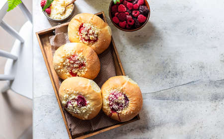 Homemade Sweet Yeast Buns filled with Berry and with crumble. Concrete bsckground. Copy space, top view.