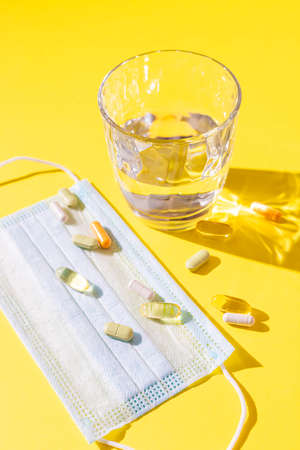 Protective face masks, medicinal pills and a glass of water on a yellow background with sunlight shadow. Supporting immune system in season of flu or coronavirus. Space for text.