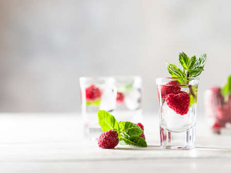 Raspberry vodka glass shot with fruit inside. Fresh summer shots for party. Berries in alcohol glass. Glass of sparkling water. Alcohol shots