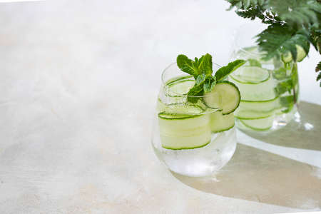 Detox cocktail cucumber and mint on a light background. Healthy nutrition diet concept. Homemade lemonade. Cold and refreshing detox water. Copy space Imagens