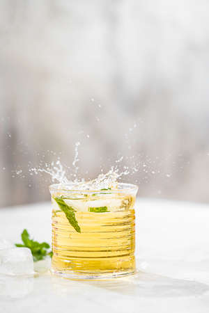 Summer iced green tea with fresh mint on light table. Food in motion concept. Summer cold drink cocktail. Copy space Imagens