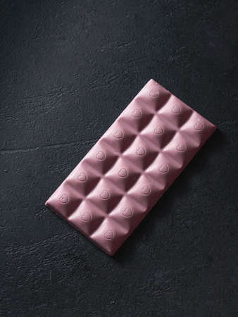 Pink chocolate on a black background. Ruby chocolate. The fourth type in chocolate. Selective focus