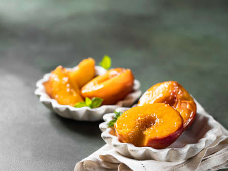 Caramelized peaches with honey, with mint leaves on a concrete background with shadows. Summer dessert. Banque d'images