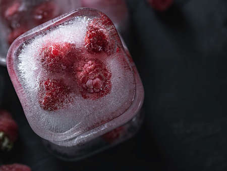 Raspberry frozen in the ice cube on black background. Fresh healthy summer eating.