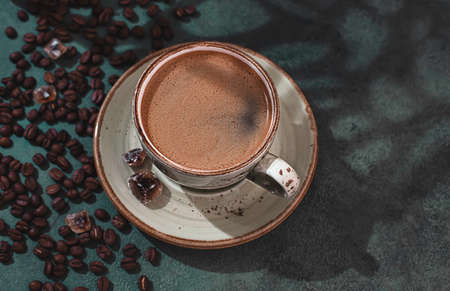 Fragrant strong coffee and coffee beans on a dark green concrete background. The concept of hot drinks. Copy space for your text