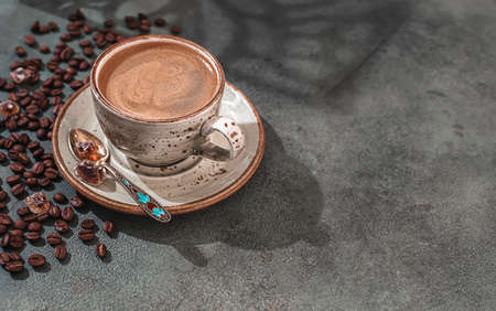 Fragrant strong coffee and coffee beans on a dark green concrete background. The concept of hot drinks. Banque d'images