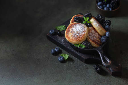 Curd pancakes or syrniki with fresh berries on a concrete background. Ukrainian, Russian cuisine sweet food. Delicious healthy breakfast. Selective focus