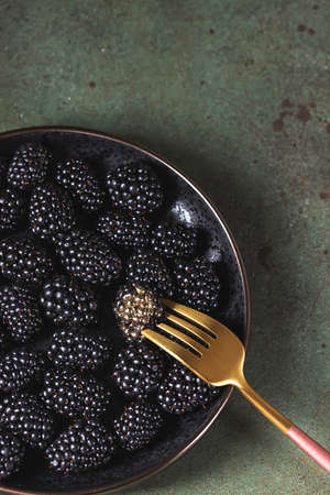 Fresh ripe blackberries as background, top view. Food concept. Blackberries decorated with edible gold powder. The concept of luxury is extraordinary. Top view.