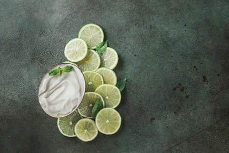 Jar with cosmetic product with lime and mint halves on green concrete. Natural citrus cosmetics with vitamin C. Copy space.