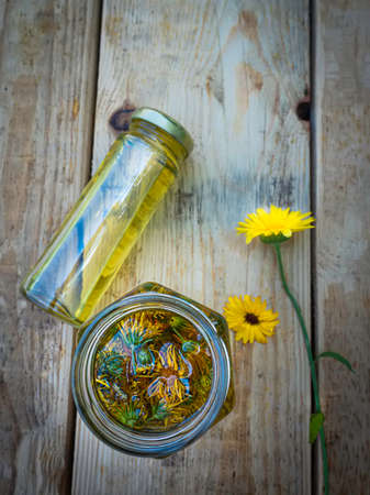 Bottles and dried calendula officinalis petals with macerated oil on wooden background. Banque d'images