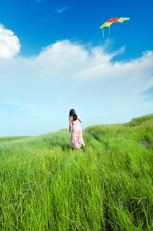 Blue sky, wearing a skirt girl flying a kite in the grasslands.