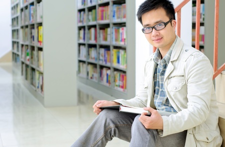 Handsome man sitting and reading in library Stock Photo - 10874260