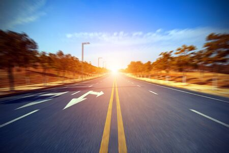 side road: Asphalt blurry road and bright blue sky with clouds Stock Photo