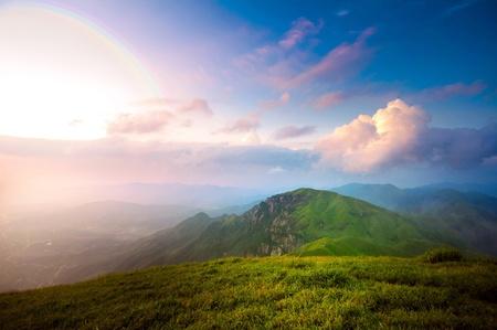 majestueuze zonsondergang wolken en pad door een bergweide aan horizon