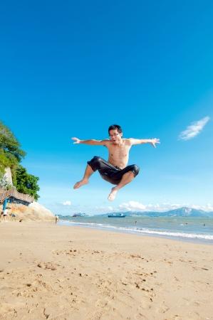 nue plage: L'homme de sauter sur une plage tropicale Banque d'images